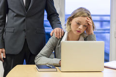 Portrait of sad businesswoman with her boss at background. Hand Royalty Free Stock Photos