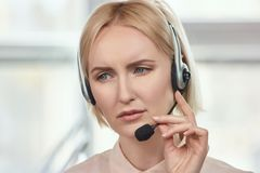 Portrait of sad call center operator. Blond mature woman with frown face dissapoint with something Royalty Free Stock Images