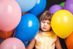 Sad blond little girl with colorful balloons. Portrait of sad Caucasian blond little girl with colorful balloons over black background Royalty Free Stock Photos