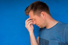 Portrait of a sad caucasian man with heavy thoughts or head ache. On blue background Stock Photos