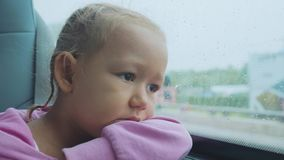 Portrait of sad child looking out the wet window, while travelling by bus.