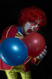 Portrait of a sad clown holding two balloons Royalty Free Stock Photo