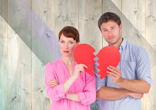 Portrait of sad couple holding broken hearts. Against wooden background Stock Photo