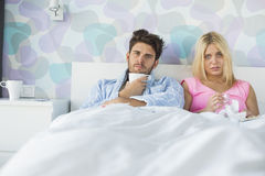 Portrait of sad couple holding coffee mug and glass while relaxing on bed royalty free stock photo