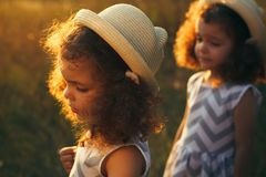 Portrait of a sad curly little girl and her twin sister. Little girl hurt. Toddler girls in hats with sunset warm light stock image