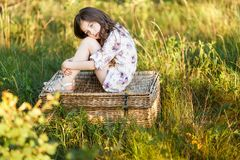 A portrait of a sad cute little girl west sitting on a basket outside at sunset royalty free stock photography