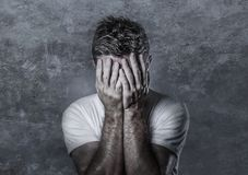 Portrait of sad and depressed man covering face with hands looking desperate feeling frustrated and helpless in depression and sad. Ness facial expression Royalty Free Stock Photos