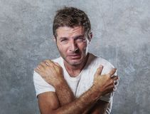Portrait of sad and depressed man hugging and embracing himself desperate feeling frustrated and helpless in depression and sadnes. S facial expression concept Royalty Free Stock Images