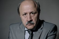Portrait of sad and depressed senior mature business man on his 60s suffering depression looking lost and thoughtful wearing neckt. Ie isolated on dark stock image