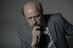 Portrait of sad and depressed senior mature business man on his 60s suffering depression looking lost and thoughtful wearing neckt. Ie isolated on dark stock photo
