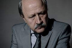 Portrait of sad and depressed senior mature business man on his 60s suffering depression looking lost and thoughtful wearing neckt. Ie isolated on dark royalty free stock photography