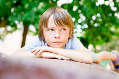 Portrait of sad dreaming little boy outdoors. In public park Royalty Free Stock Image
