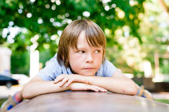 Portrait of sad dreaming little boy outdoors. In public park Royalty Free Stock Images