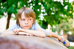 Portrait of sad dreaming little boy 7 years old outdoors. Portrait of sad dreaming little boy outdoors in public park Royalty Free Stock Image