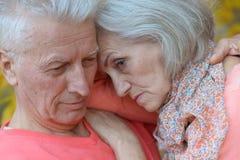 Portrait of a sad elder couple in autumn park Stock Photos