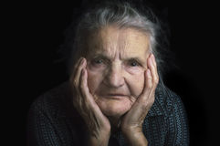 Portrait of a sad elderly woman. Dreaming the past. Royalty Free Stock Image