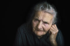 Portrait of a sad elderly woman. Dreaming the past. Stock Image