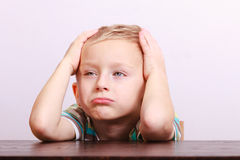 Portrait of sad emotional blond boy child kid at the table. Portrait of sad unhappy tired blond boy. Child kid making silly funny face at the table interior Stock Photography