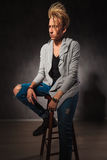 Portrait of sad fashionable man posing in studio background. While sitting on a chair Stock Images