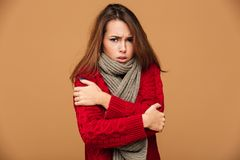 Portrait of sad freezing brunette woman in red knitted sweater s. Hivering while hugging herself, looking at camera,  on beige background Stock Photos