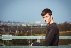 Portrait of sad frowning young man. Portrait of sad and gloomy frowning young man standing on the bridge under city road Stock Photography