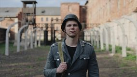 Portrait of a sad German soldier standing in front of a concentration camp. The Second World War reenactment stock video footage