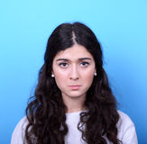 Portrait of sad girl against blue background Stock Images