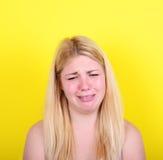 Portrait of sad girl against yellow background Stock Image