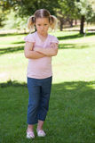 Portrait of a sad girl with arms crossed at park Royalty Free Stock Image