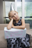 Portrait of sad girl with birthday gift sitting on sofa at home Stock Photography