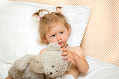 Portrait of a sad girl child sitting on a bed in the bedroom with a toy. Kid waking up in bed unhappy. Time to bed. Portrait of sad girl child sitting on a bed Stock Photos