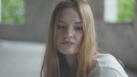 Portrait of sad girl with long red hair in a big dusty empty room in the abandoned building feeling bad. Portrait of a sad girl with long hair in a big dusty stock video