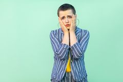 Portrait of sad handsome beautiful short hair young stylish woman in casual striped suit standing nervous holding her face and stock photo