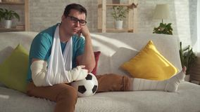 Portrait sad injured athlete sitting on the couch with a soccer ball stock video