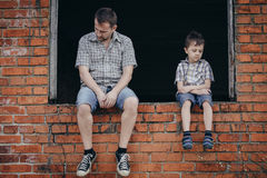 Portrait of sad little boy and father. Portrait of young sad little boy and father sitting outdoors at the day time. Concept of sorrow royalty free stock images