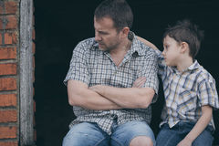 Portrait of sad little boy and father. Portrait of young sad little boy and father sitting outdoors at the day time. Concept of sorrow stock photography