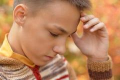 Sad boy outdoors. Portrait of a sad little boy outdoors in autumnal park Stock Photo