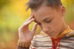 Sad boy outdoors. Portrait of a sad little boy outdoors in autumnal park stock photos