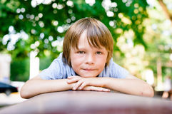 Portrait of sad little boy outdoors. In public park Royalty Free Stock Photo