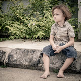 Portrait of a sad little boy. Sitting on the road at the day time royalty free stock photography