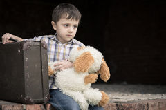 Portrait of sad little boy. Portrait of young sad little boy sitting with suitcase outdoors at the day time. Concept of sorrow royalty free stock photography