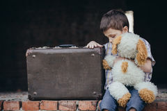 Portrait of sad little boy. Portrait of young sad little boy sitting with suitcase outdoors at the day time. Concept of sorrow stock photos