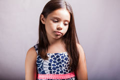 Portrait of a sad little girl. Little Hispanic girl looking all sad in a white background Stock Photography