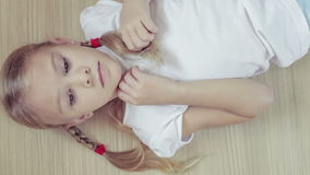 Portrait sad little girl lying on floor at home. At the day time stock footage