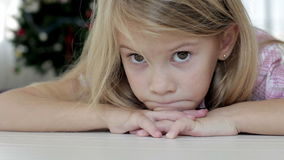Portrait of sad little girl. Lying on floor at home at the day time stock video footage