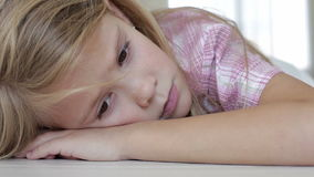 Portrait of sad little girl. Lying on floor at home at the day time stock video