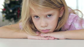 Portrait of sad little girl. Lying on floor at home at the day time stock footage