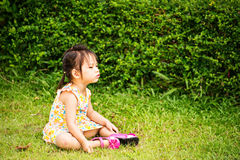 Portrait of sad little girl playing in summer park Stock Image