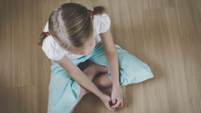 Portrait sad little girl sitting on floor at home. At the day time stock video footage