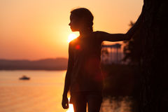 Portrait of sad little girl standing on the beach. At sunset time Stock Images
